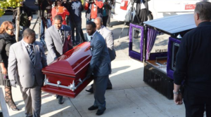 Tyshawn's body being carried inside red casket.